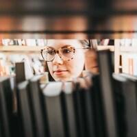 Elle cherche des livres dans un rayon.