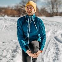 Un jeune homme en tenue de course d'hiver, dehors dans la neige, tient son genou plié entre ses mains.