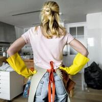 Une femme de dos, les mains sur les hanches, avec des gants et un tablier, devant une cuisine en désordre.