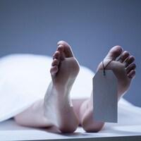 Photo des pieds d'une personne allongée sur une table recouverte d'un drap, avec une étiquette au pied.