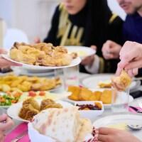 Des personnes rassemblées autour d'une table sur laquelle se trouve plusieurs plats de viande, de feuilletés et de fruits séchés.