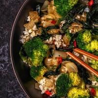 Vue aérienne d'un plat de légumes servi sur du riz, dans un grand bol, avec des baguettes.