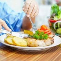 Un homme coupe un morceau de viande dans une assiette.