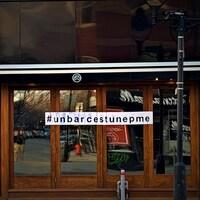 Une affiche avec le mot-clic « Un bar, c'est une pme » est collée sur la devanture d'un bar fermé.