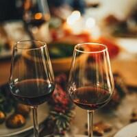 Deux verres de vin rouge posés sur une table de Fêtes avec des bougies.