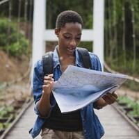 Photo d'une femme qui lit une carte sur un pont dans une forêt.