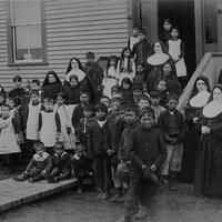 Groupe d'élèves, religieuses et hommes autochtones posant devant l'école, foyer fédéral de Port Harrison (Inukjuak),   Québec, vers 1890