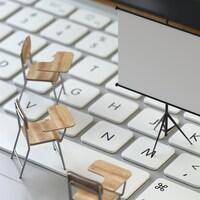 Un tableau blanc et des bancs d'école miniatures sont posés sur un clavier d'ordinateur.