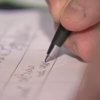 Une personne appose sa signature sur un document.