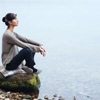Une femme assise au bord d'un lac regarde au loin d'un air calme et serein.