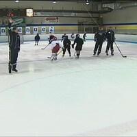 Elle lève la main sur la glace, sifflet à la bouche, alors que plusieurs joueurs s'activent