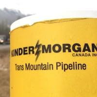 Logo de l'entreprise Kinder Morgan en premier plan, en bordure d'une route.