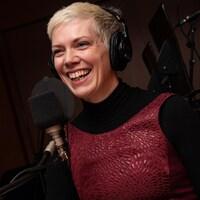 La femme aux cheveux platine courts sourit au micro de l'émission.