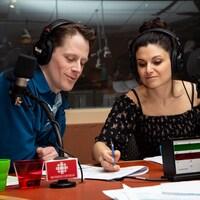 Les deux comédiens sont vus à la table de l'émission, devant leur micro, en train de noter sur une feuille blanche.