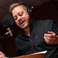 En pleine lecture de son texte au micro de l'émission, le comédien gesticule.