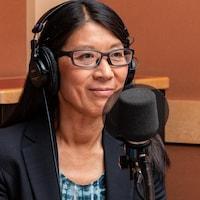 Une femme portant lunettes et casque d'écoute sourit devant un micro.