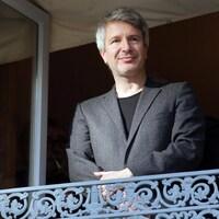 Un homme portant un veston gris est debout sur un balcon.