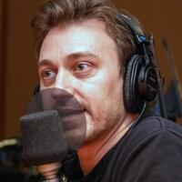 L'acteur Benoît McGinnis parle devant un micro.