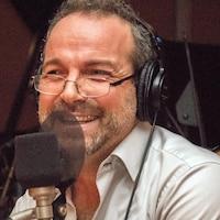 L'auteur Michel Duchesne sourit devant un micro.
