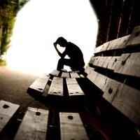 Une personne est accoudée sur ses genoux, assise sur un banc à l'orée d'un tunnel.