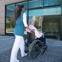 Une femme pousse le fauteuil roulant d'un homme à l'entrée d'un édifice.