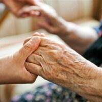 Une personne tient les mains d'une aînée.