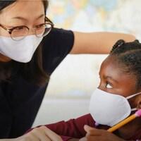 Une enseignante parle à une élève. Toutes les deux portent un masque.