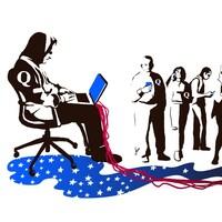 Un homme arborant la lettre Q sur son chandail utilise un ordinateur d'où s'étendent des tentacules en forme de drapeau américain.