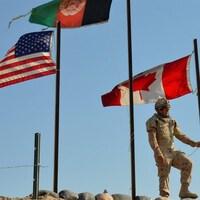 Un soldat en habit de camouflage met un drapeau en berne.