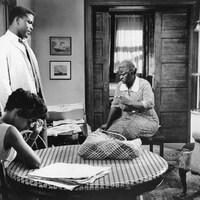 La photo en noir et blanc de quatre personnes dans un salon.