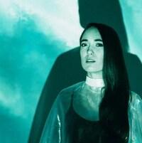 La chanteuse devant un mur turquoise