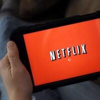 L'écran d'une tablette, tenue par un homme dont on aperçoit les pieds en arrière plan, affiche le logo de Netflix.