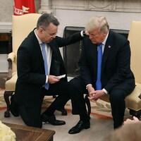 Le pasteur Andrew Brunson, qui a un genou par terre, met sa main sur l'épaule de Donald Trump, qui est assis.