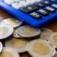 Des pièces de 2 dollars canadiens sur une table, à côté d'une calculatrice.