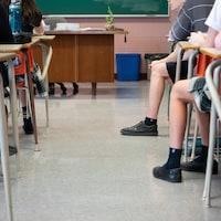 Des élèves du secondaire vus de dos dans une classe à la hauteur des jambes et des pieds, de manière à ne pouvoir les identifier.