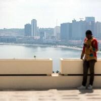 Un homme regarde son téléphone alors que se profile derrière lui Luanda, en Angola.