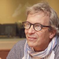 Alain Choquette, portant un foulard et des lunettes rondes, sourit au micro du studio 18