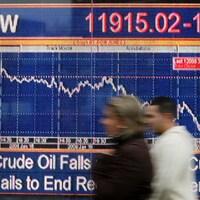 Des passants marchent devant un écran affichant l'indice FTSE, en janvier 2008.