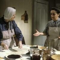 Monique Aubry et Nicole Leblanc en train de cuisiner debout autour d'une table.
