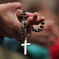 Les mains jointes, une paroissienne tient un chapelet avec une croix bien visible au bout de la chaîne.
