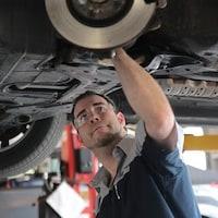 Un homme inspecte le châssis d'une voiture.
