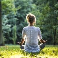 Une femme qui médite dans un parc.