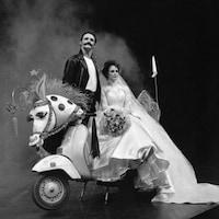 Les deux acteurs se tiennent sur un scooter décoré d'une tête de cheval de carnaval, Goldie Semple porte une robe de mariée et Colm Feore porte un blouson de cuir.
