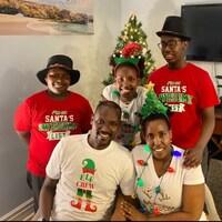 Thérence  Maxime Ntunga et sa famille posent devant un arbre de Noël.