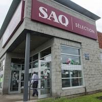 Un homme, en chemise et en pantalon, sort d'un bâtiment. Sur l'enseigne du bâtiment, on peut lire « SAQ Sélection ».