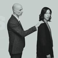 Un homme met sa main sur l'épaule d'une femme qui est dos à lui.