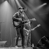 L'auteur-compositeur-interprète Scott-Pien Picard sur scène, avec sa guitare.