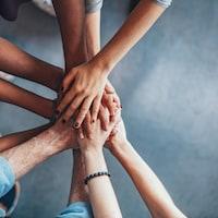 Des jeunes unissent leurs mains pour démontrer leur amitié.