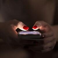 Un gros plan sur les mains d'une femme tenant un téléphone intelligent. Les ongles rouges de la femme sont éclairés par l'écran.