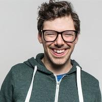 Un homme très souriant porte des lunettes et une veste à capuchon.